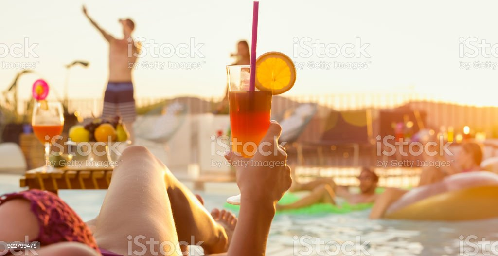 Frau liegend Pool mit Cocktail in der Hand, während andere Menschen tanzen in und rund um Pool bei Sonnenuntergang – Foto