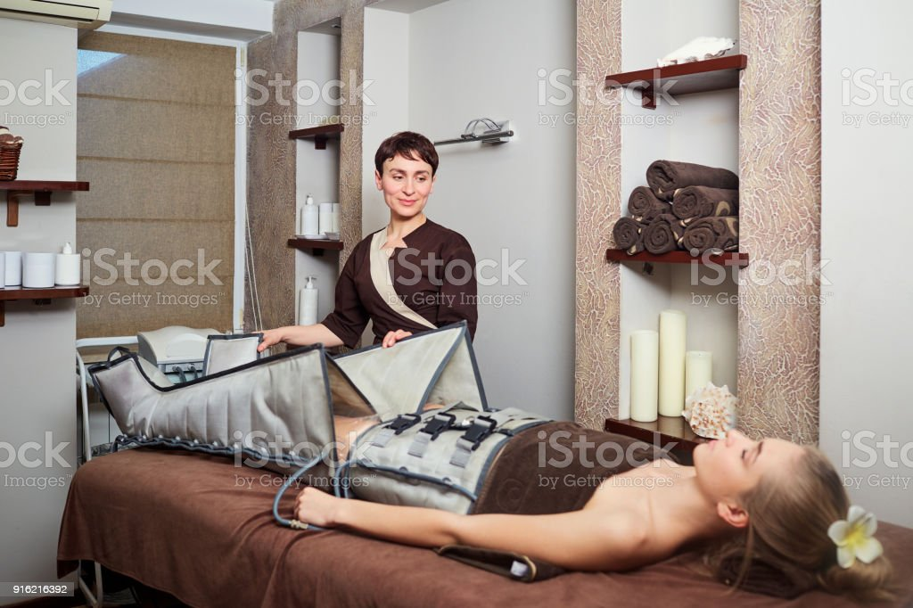 A woman lying down doing pressotherapy treatment stock photo