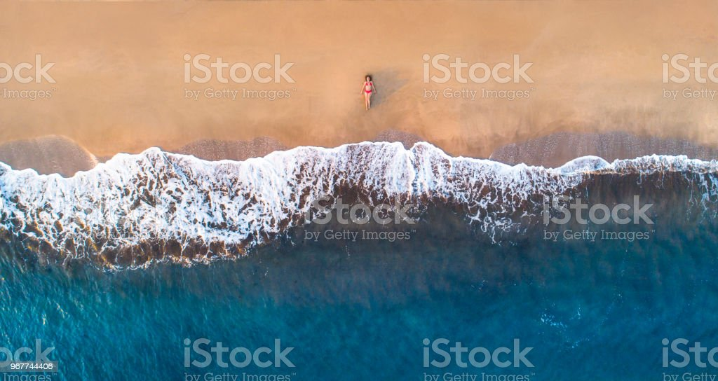Woman lying down on sandy beach at summer stock photo