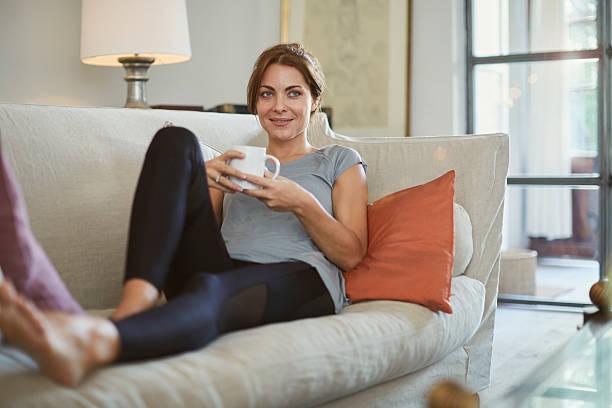 Woman lying down on the sofa and enjoying tea. stock photo