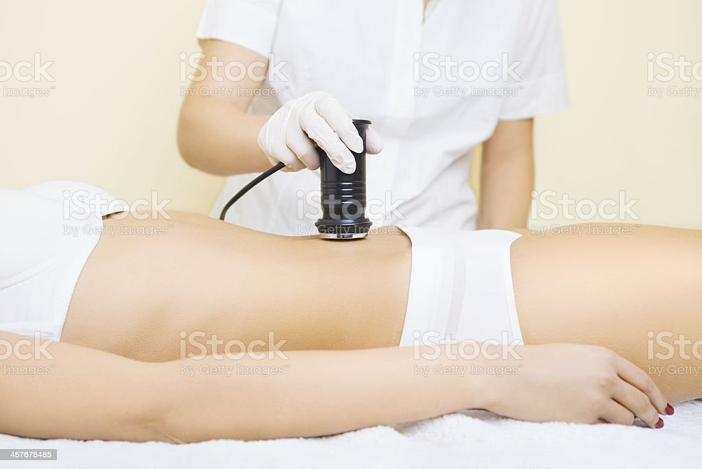 Woman lying down receiving a cavitation treatment stock photo