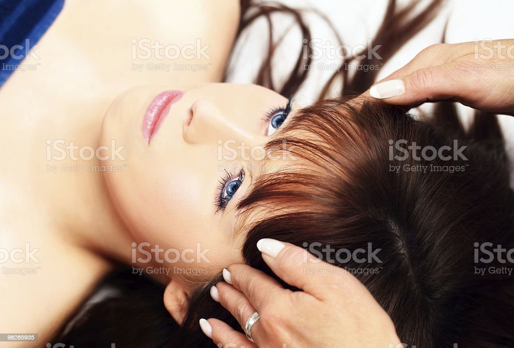 Woman lying, gets massage, reiki,acupressure on her head royalty-free stock photo