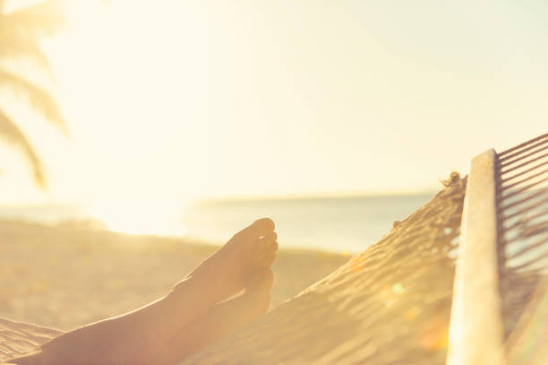 woman lying in a hammock on the beach. - woman leg beach pov stock photos and pictures