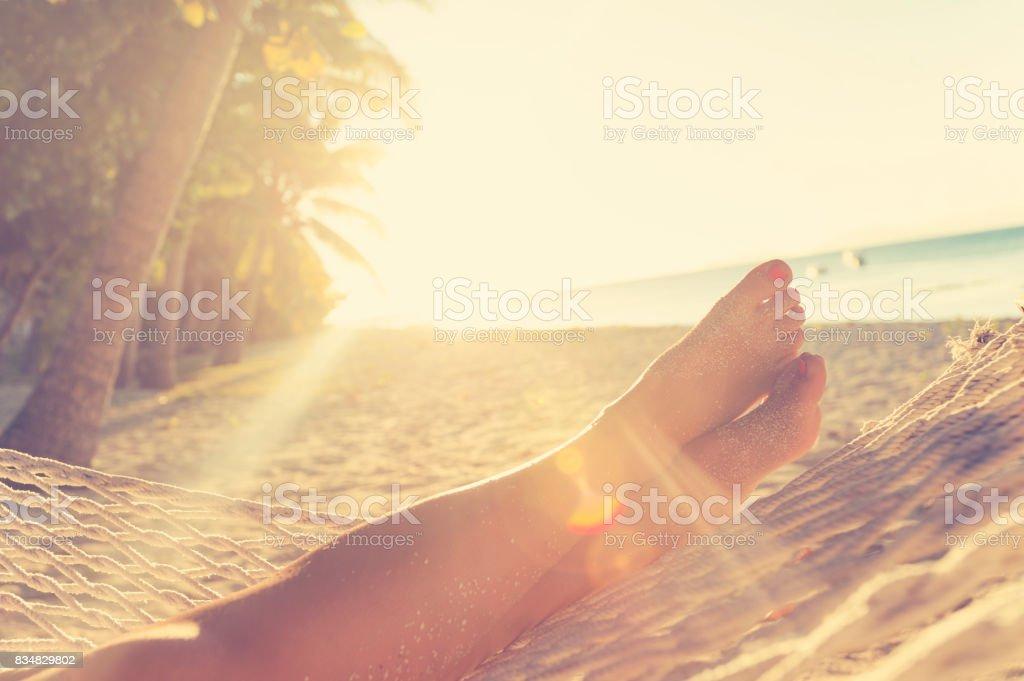 Woman lying in a hammock on the beach. stock photo