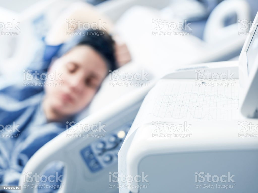 Woman lying in a hospital bed stock photo
