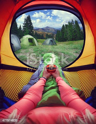 497486952 istock photo Woman lying in a tent with coffee 477974820