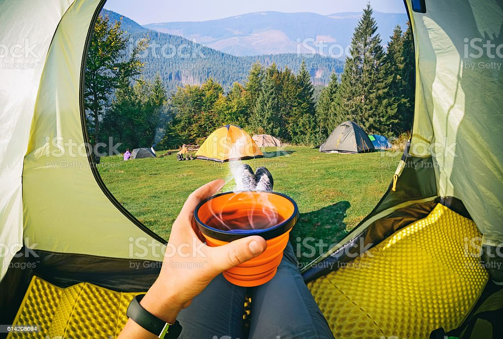 Woman lying in a tent with coffee stock photo