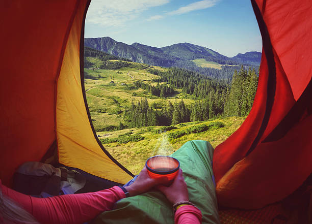 Woman lying in a tent with coffee ,view of mountains stock photo