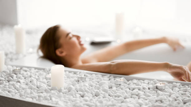 Woman Lying In Bath With Foam And Candles Enjoy Spa Procedure. Woman Lying In Bath With Foam And Candles taking a bath stock pictures, royalty-free photos & images