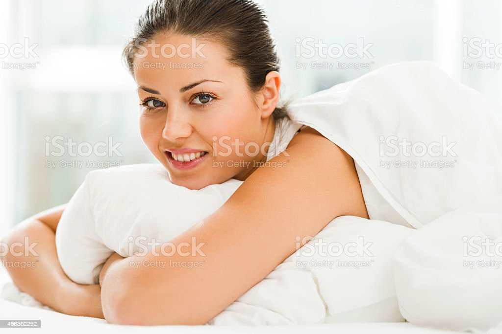 Woman lying in bed and looking at the camera. royalty-free stock photo