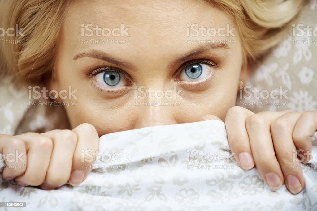 Woman lying in bed doesn't want to wake up royalty-free stock photo