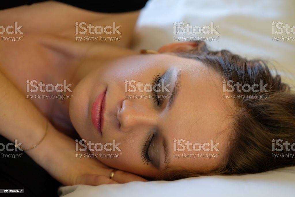 Woman lying in bed, eyes closed and smiling stock photo