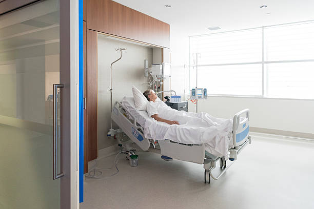 Woman lying in bed on hospital ward stock photo