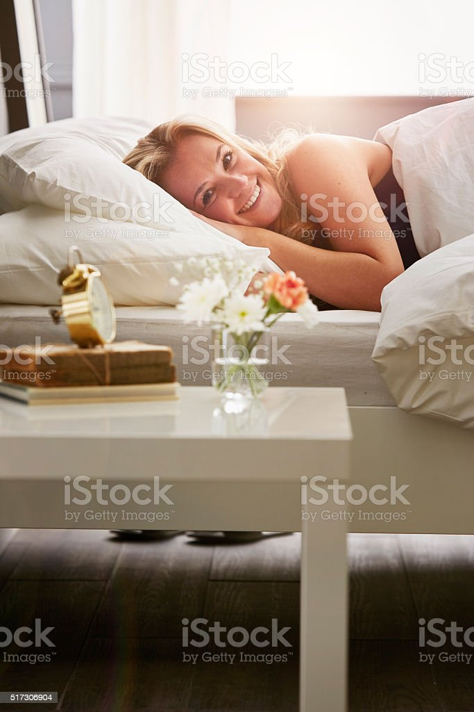 Woman lying in bed stock photo