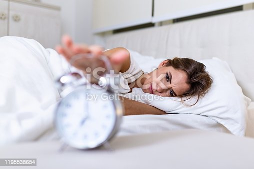 Woman lying in bed turning off an alarm clock in the morning at 7am. Hand turns off the alarm clock waking up at morning, girl turns off the alarm clock waking up in the morning from a call.