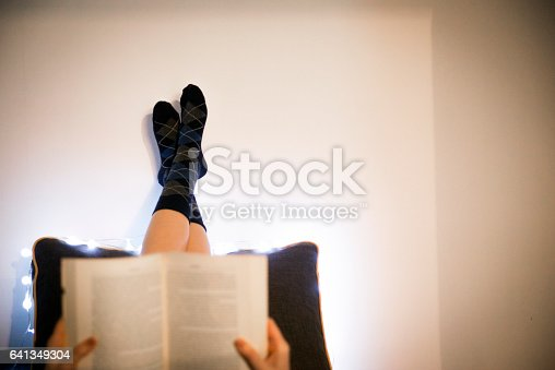 501914364istockphoto Woman lying in bed while reading a book 641349304
