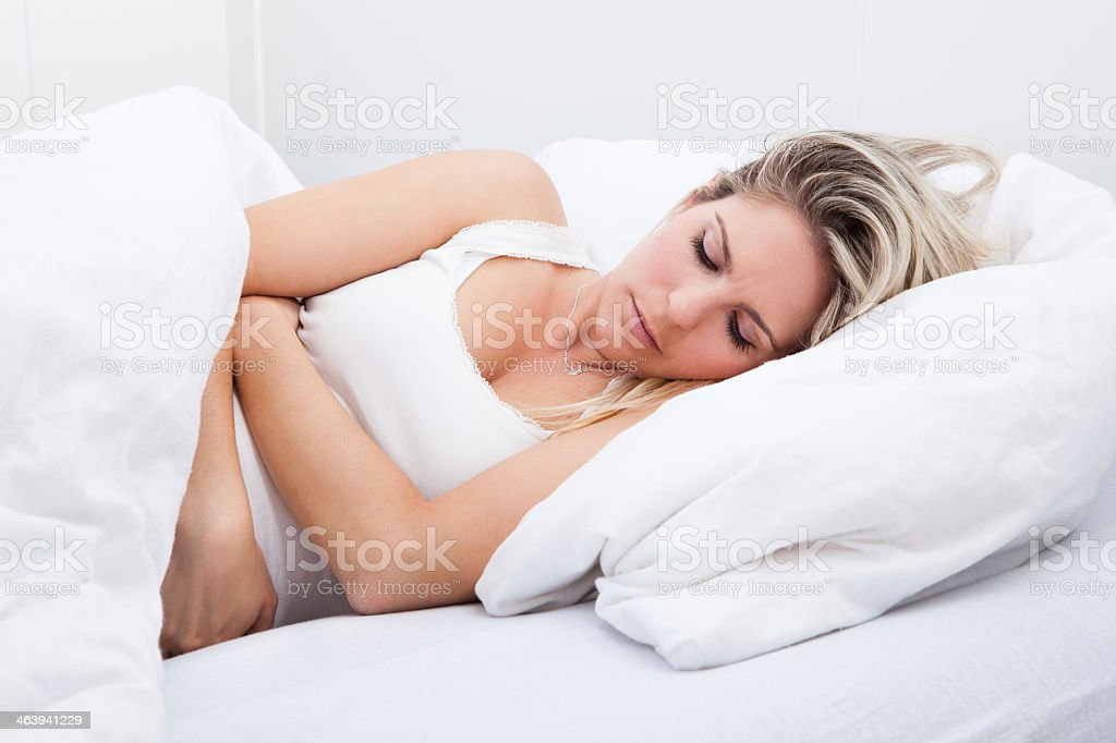 Woman lying in bed with a stomachache stock photo