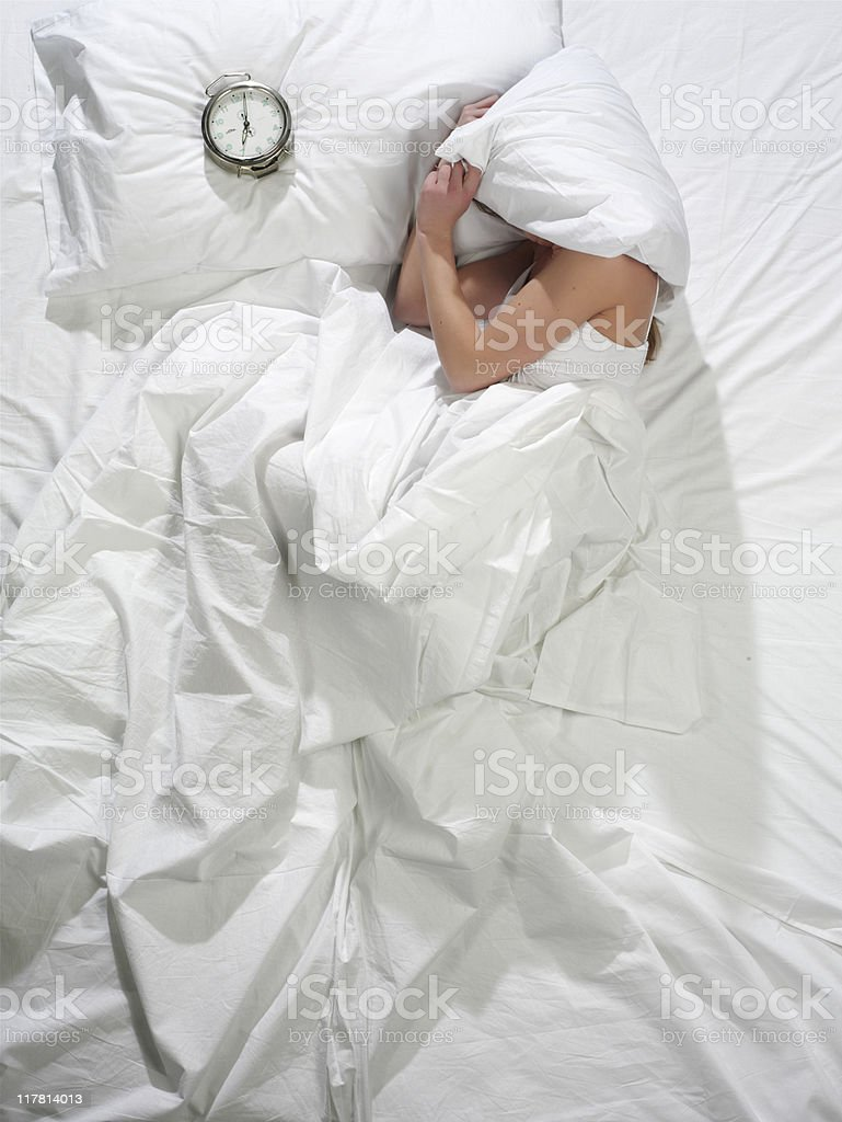 A woman lying in bed with white sheets royalty-free stock photo
