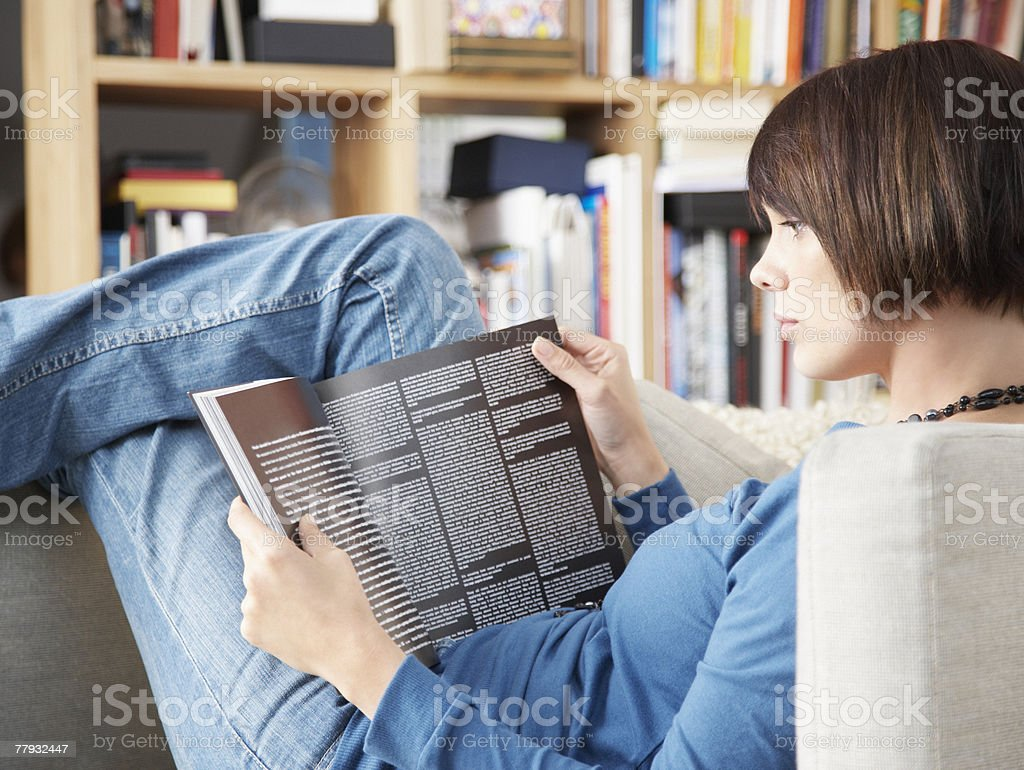 Woman lying in chair reading