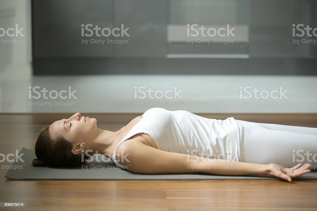 Woman lying in Corpse exercise stock photo