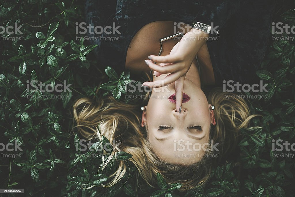 Woman lying in green plants outdoors stock photo