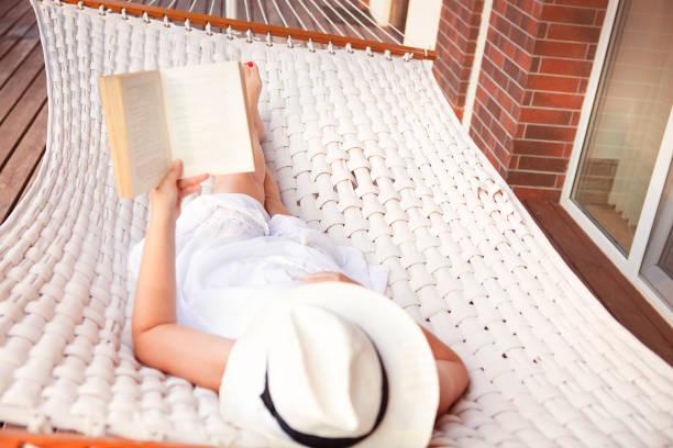 mulher deitada na rede e lendo livro - escapismo - fotografias e filmes do acervo
