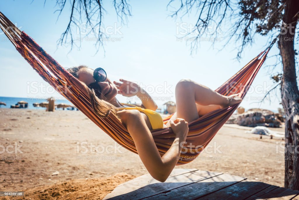 Woman lying in hammock close to the beach stock photo