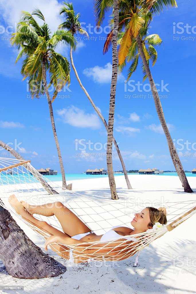Woman lying in hammock near the palm trees. royalty-free stock photo
