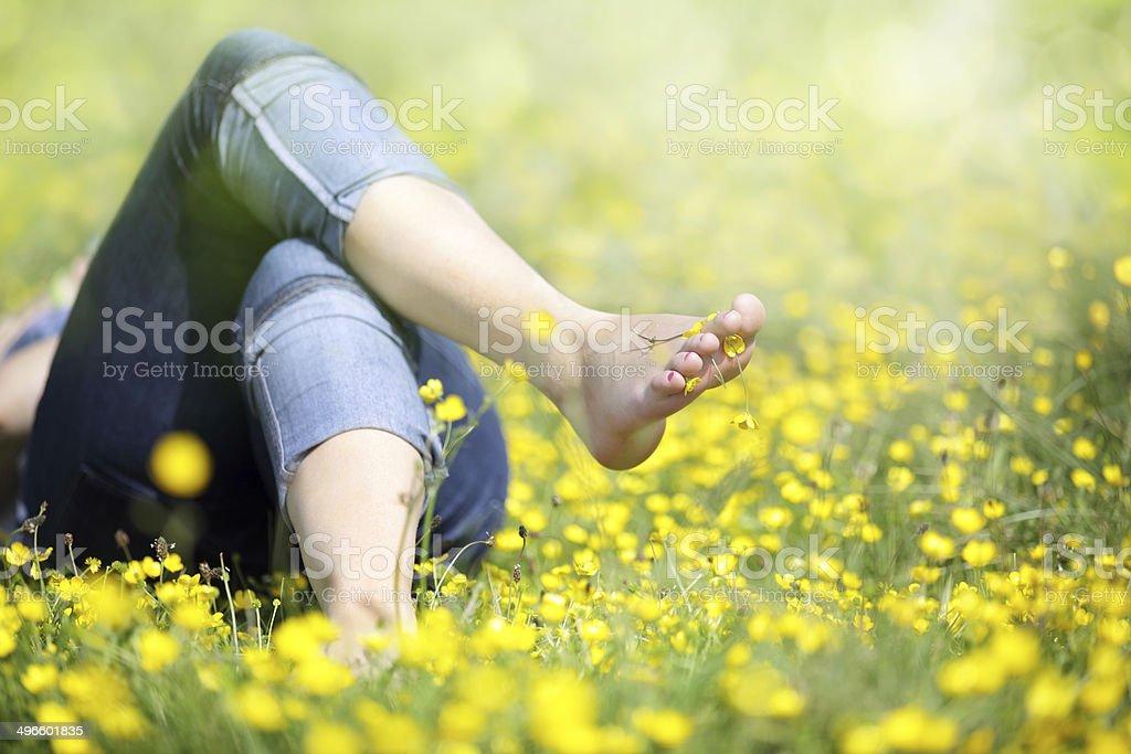 Woman lying in meadow relaxing stock photo