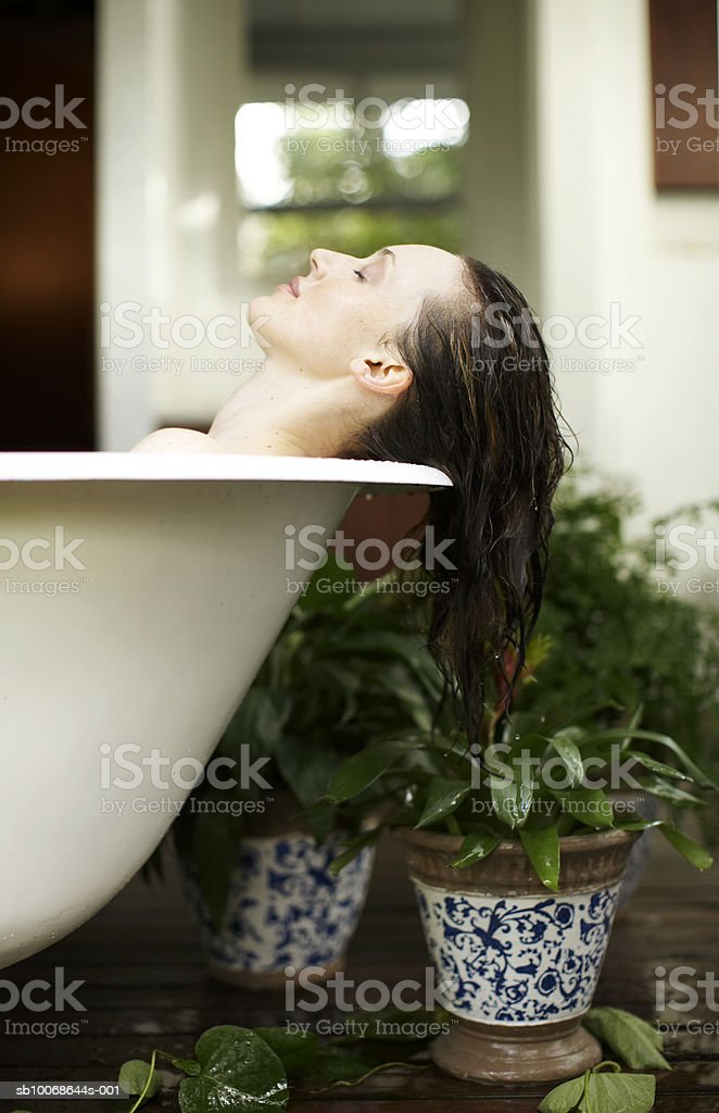 Woman lying in outdoor bath, eyes closed royalty free stockfoto
