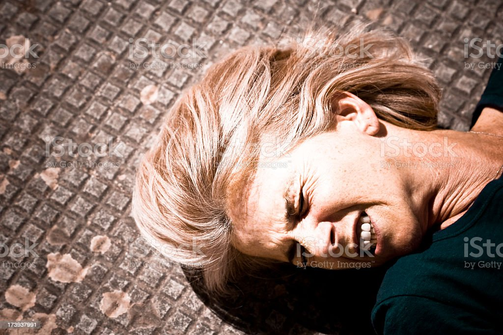 A woman lying in pain on a tile floor stock photo