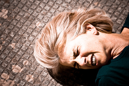 A Woman Lying In Pain On A Tile Floor Stock Photo - Download Image Now