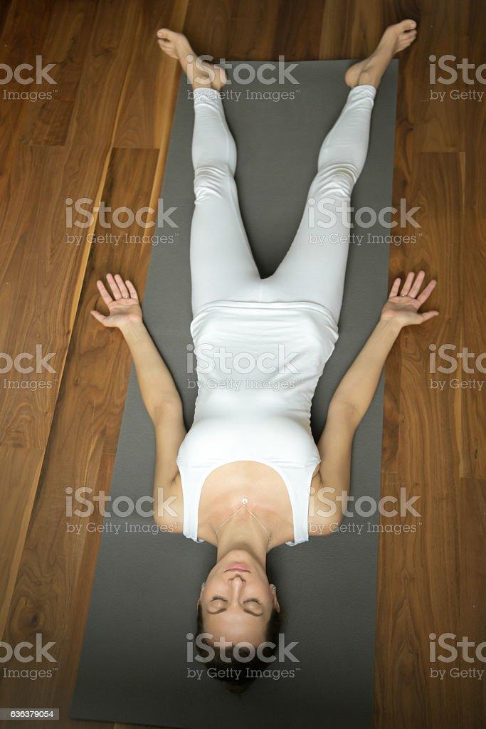 Woman lying in Savasana pose stock photo