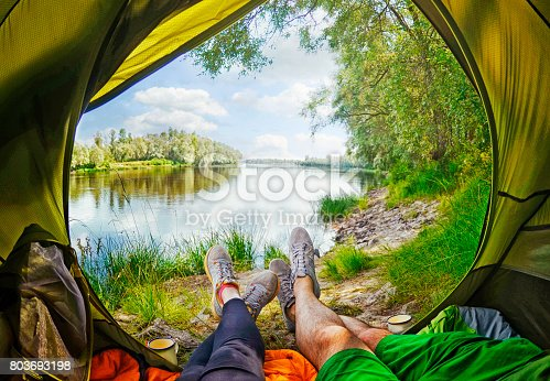 istock Woman lying in tent with a view of mountain and sky 803693198