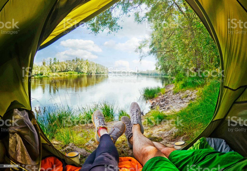 Woman lying in tent with a view of mountain and sky stock photo