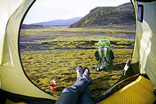 Woman lying in tent with a view of mountain stock photo