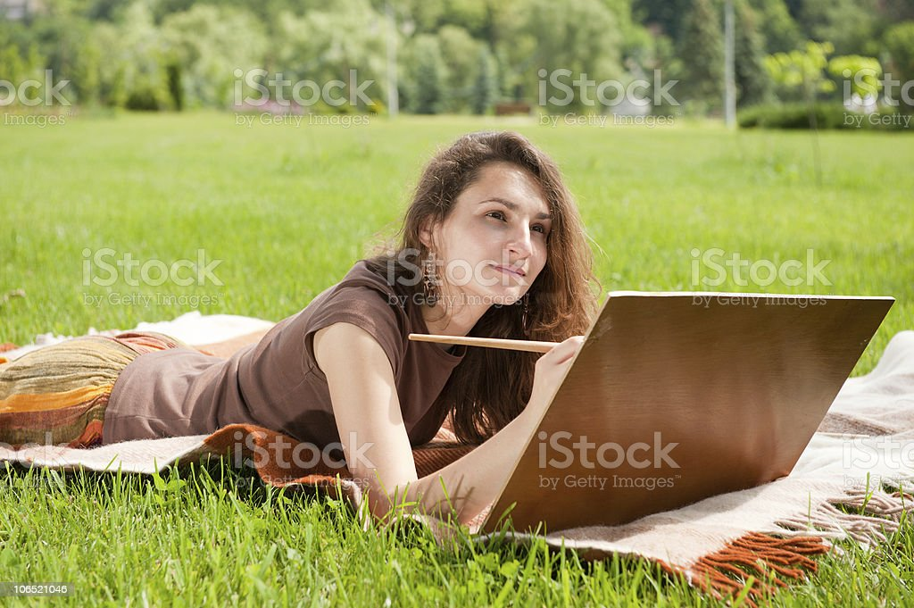 Woman lying in the grass painting royalty-free stock photo