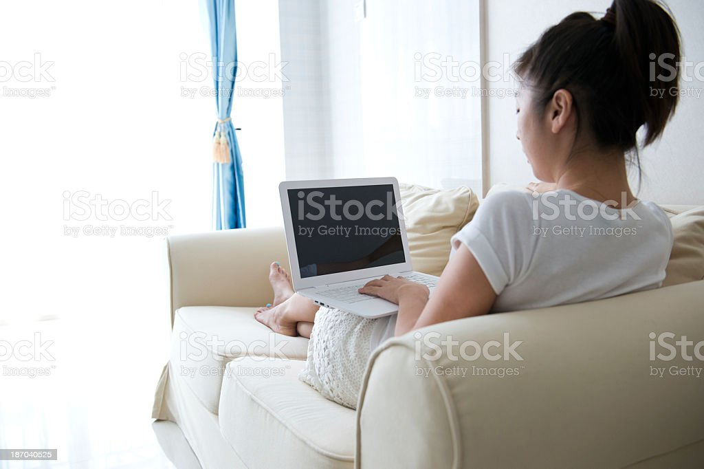 Woman lying lengthwise on sofa in bright room using laptop royalty-free stock photo