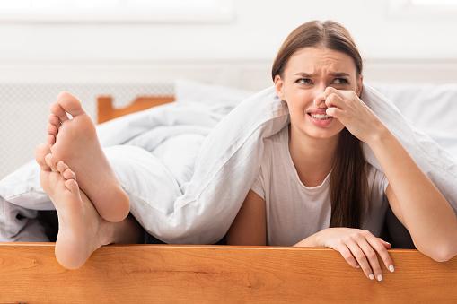 woman-lying-near-boyfriends-feet-pinching-nose-in-bed-indoor-picture-id1202954714?b=1&k=6&m=1202954714&s=170667a&w=0&h=aZD91TTQ0q-dLNADAoBnsWnUBlMB7mue_URL8H1YmlU=