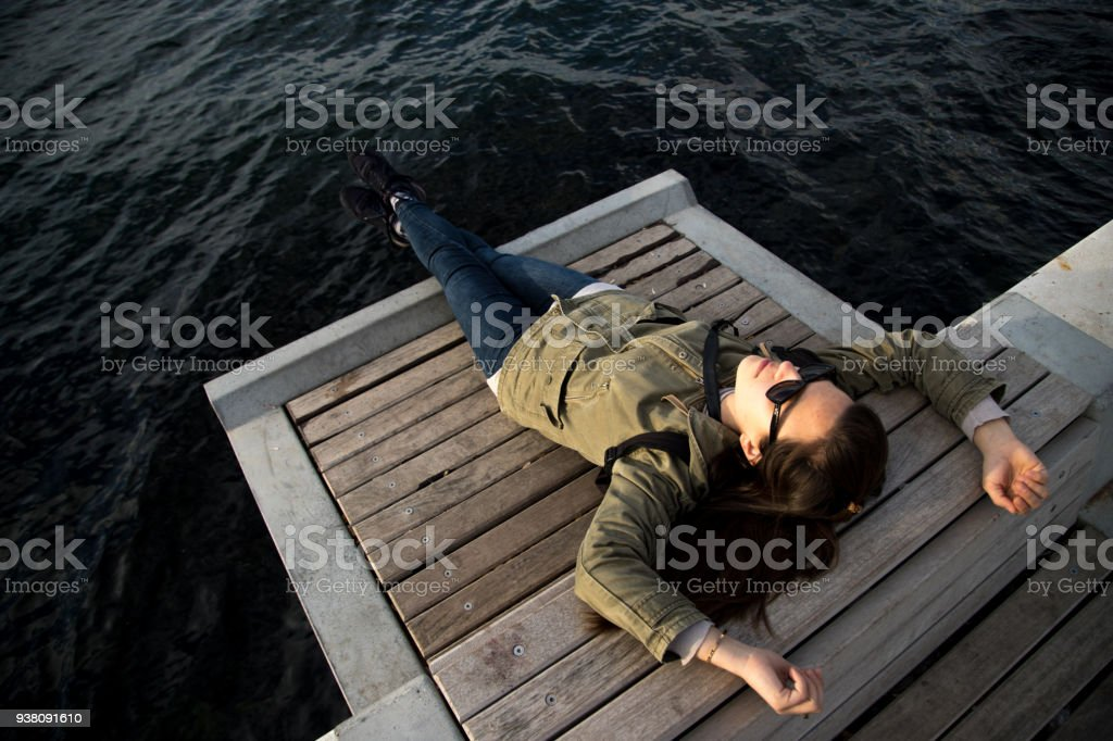 Woman lying on a bench stock photo