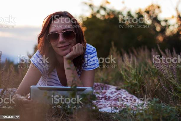 Photo of Woman lying on a blanket with tablet