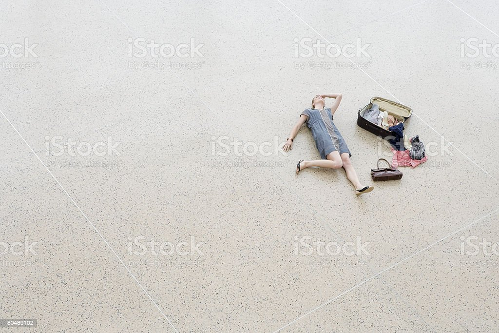A woman lying on a floor with an open suitcase royalty-free stock photo