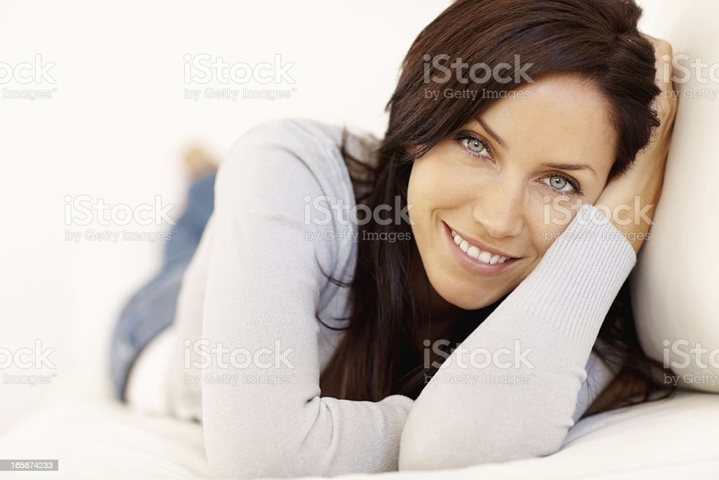 Woman lying on a sofa and smiling stock photo