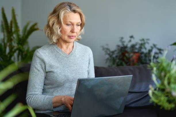 Mujer acostada en un sofá en casa concentrándose mientras trabaja en una computadora portátil. - foto de stock