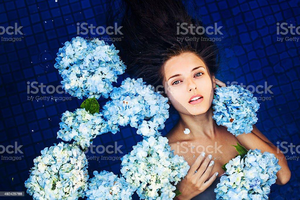 Женщина, лежа на спине в плавательный бассейн в окружении цветов стоковое фото