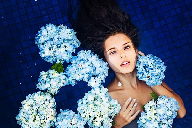 Cтоковое фото Женщина, лежа на спине в плавательный бассейн в окружении цветов