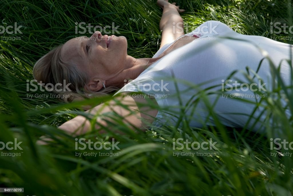 Woman lying on back in tall grasses stock photo