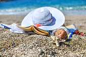 Woman lying on beach hands out starfish