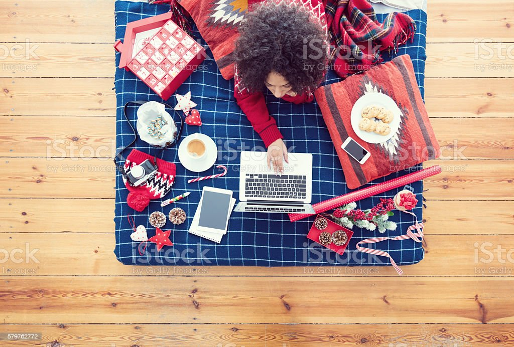 Woman lying on bed and using laptop High angle view of woman lying on the stomach on a bed and using a laptop. Winter scenery. Adult Stock Photo