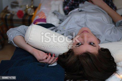 618750646istockphoto Woman lying on bed 936674700